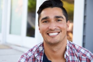 Young Man in a Flannel Shirt with a Wide and Bright Smile